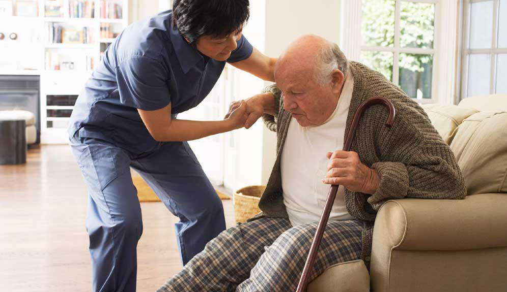 home health aide helping elderly man with an activity of daily living mobility