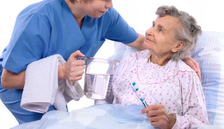 Healthcare provider helping elderly person with brushing teeth - ADL